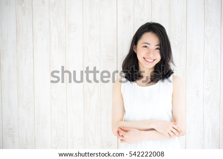 beautiful young woman against white wooden wall Royalty-Free Stock Photo #542222008