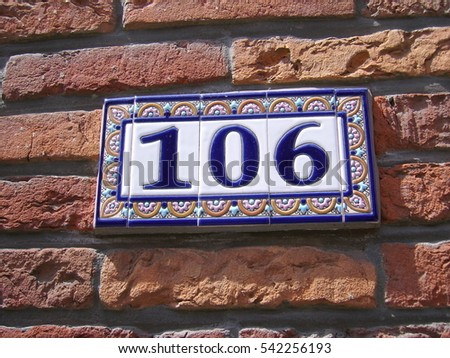 House number 106: ceramic sign with blue numbers and floral border