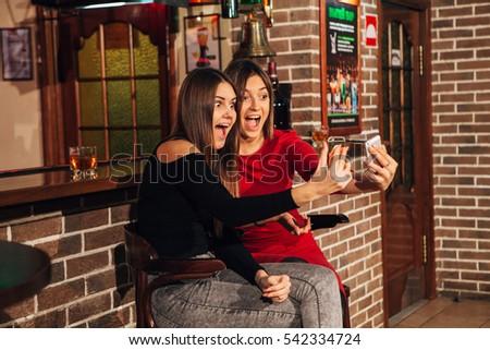 two beautiful women take a selfie at the bar #542334724