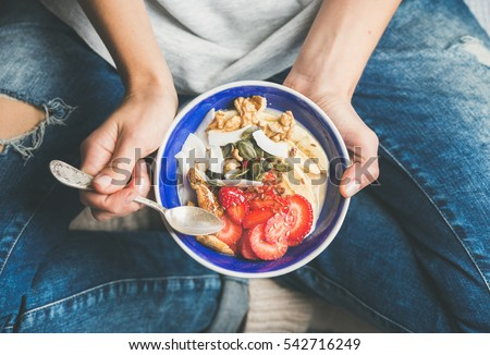 Eating healthy breakfast bowl. Yogurt, granola, seeds, fresh and dry fruits and honey in blue ceramic bowl in woman' s hands. Clean eating, dieting, detox, vegetarian food concept #542716249