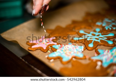 Womans hand decorating cookies with sugar. Making Gingerbread Cookies Series. #542962804