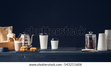 Coffee shop interior, Coffee to go and accessories on the table Royalty-Free Stock Photo #543211606