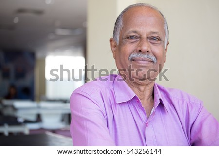 Closeup headshot portrait of elderly gentleman sitting down in pink shirt smiling, content, isolated indoors white wall background #543256144