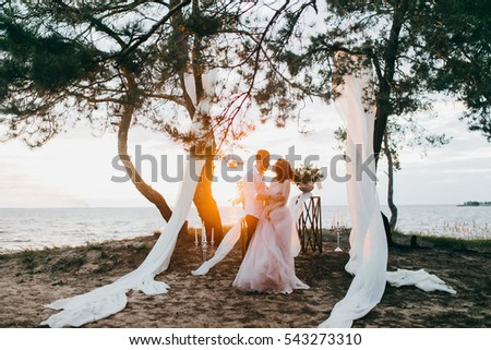 Elegant bride and groom at the evening ceremony near the ocean  #543273310
