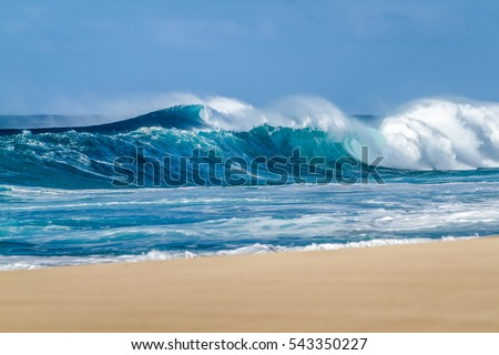 Big breaking Ocean wave on a sandy beach on the north shore of Oahu Hawaii