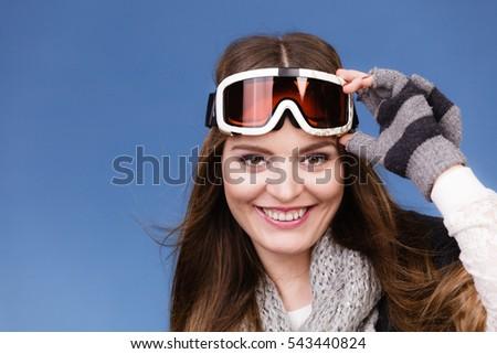 Woman skier girl wearing warm clothing ski googles portrait. Winter sport activity. Beautiful sportswoman on blue studio shot #543440824