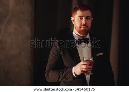 Young ginger bearded man holding a vintage glass with red wine against the light, black on background. look at the camera #543460195
