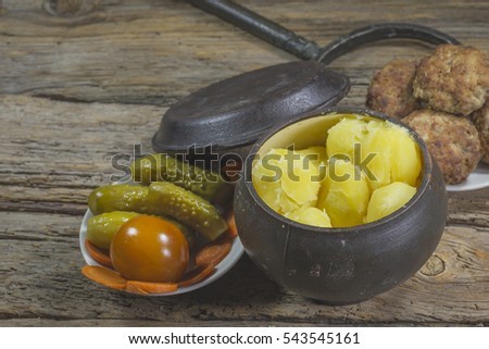 The food in the village. Boiled potatoes with meatballs and pickled cucumbers and tomatoes #543545161