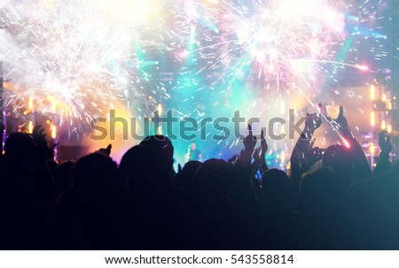 New Year concept - fireworks and cheering crowd celebrating the New year #543558814