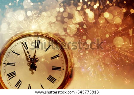 New Year's at midnight - Old clock with fireworks and holiday lights #543775813