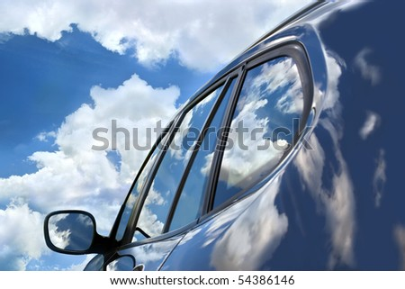 Reflections of the clouds in the polish of the brand new car. Focus is on the front car window. Reflections and the sky create deep palette of blue color in the whole picture.