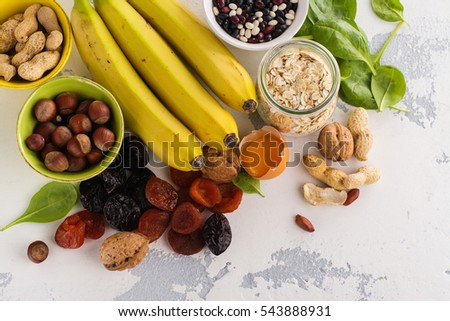 Products rich of potassium (K). Bananas, spinach, nuts, grains, dried fruits overs stone table. Space for text #543888931