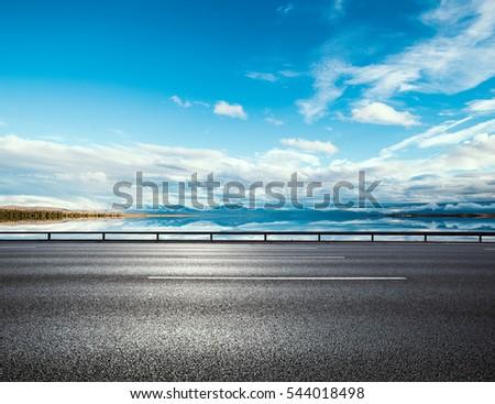 Asphalt road near water in summer #544018498