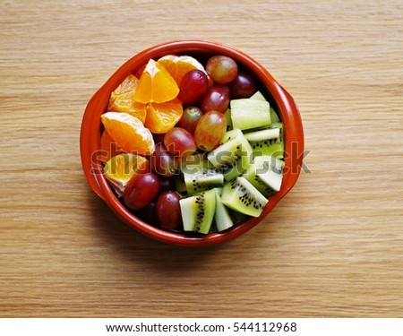 Mixed fruits in a bowl on a wooden background. Top view. #544112968