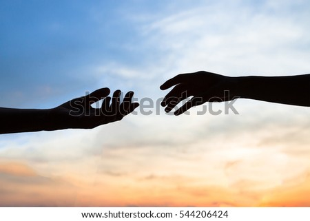 mercy, two hands silhouette on sky background, connection or help concept Royalty-Free Stock Photo #544206424