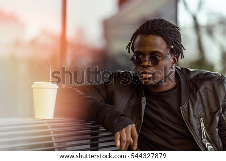 Portrait of a happy african american in sunglasses man sitting on bench drinking cup of coffee #544327879