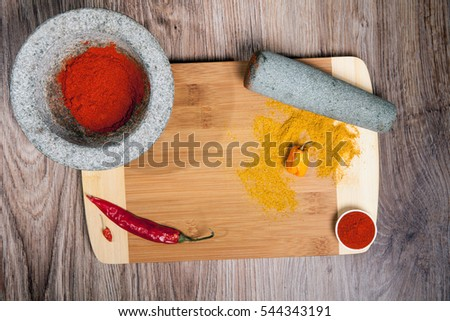 Stone mortar with paprika powder. Spices on cutting board whit hot chili and Habanero. Culinary composition on wood table background. #544343191
