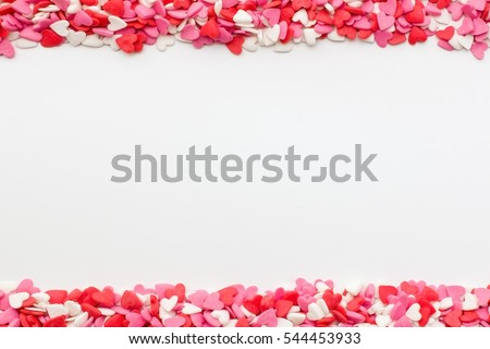 many small hearts on the top and bottom on a white background. festive background for Valentine's day, birthday, holiday.