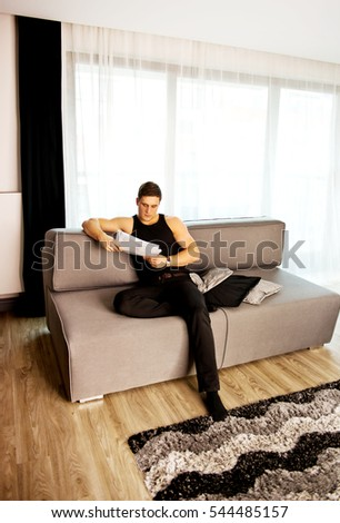 Young man sitting on sofa and reading soma papers. #544485157