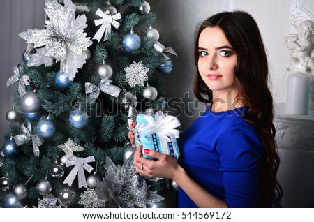 The girl in a beautiful blue dress with a Christmas present in his hands stand nearby the decorated and shiny Christmas tree. Young lovely girl in anticipation of New Year's Eve #544569172