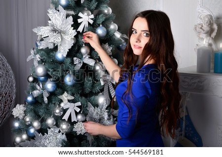 Young girl in a blue dress dresses up Christmas tree. Girl in formal attire catches spherical shiny toy on the Christmas tree. The process preparing for the celebration of the New Year and Christmas #544569181