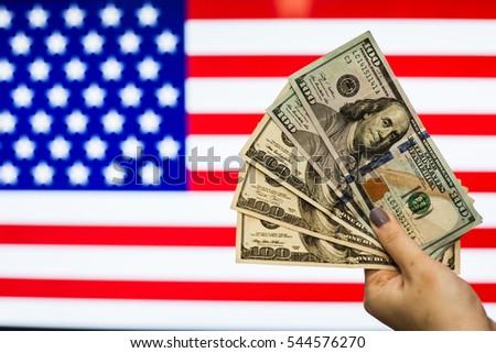 Man holding US Dollar bank note indicating market crash due to new US president with flag background #544576270