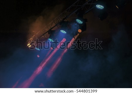 Stage lights. Several projectors in the dark. Multi-colored light beams from the stage spotlights on the stage in the smoke at the time of the entertainment show. Night club #544801399