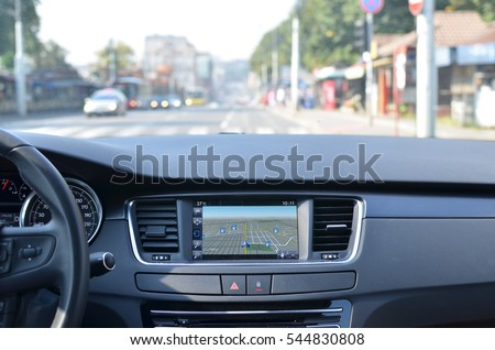 View from inside a car on a part of dashboard with a navigation unit and blurred street in front of a car Royalty-Free Stock Photo #544830808