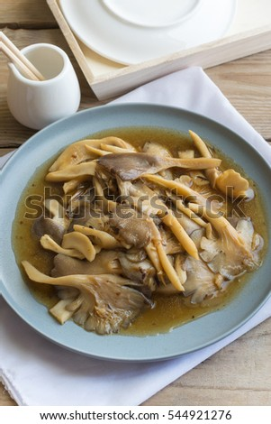Mushrooms fried in oyster sauce with gray dish and white fabric on wooden table. #544921276