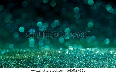 green Sparkling Lights Festive background with texture. Abstract Christmas twinkled bright bokeh defocused and Falling stars. Winter Card or invitation.