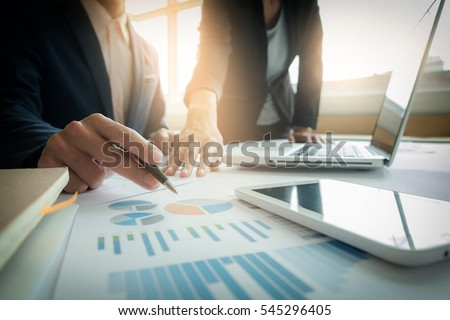 Business team two colleagues discussing new plan financial graph data on office table with laptop and digital tablet. Royalty-Free Stock Photo #545296405