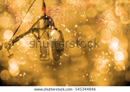 Condenser microphone with pop filter windscreen on stand ready for recording on stage in celebration event . High fidelity microphone on stage with firework display and   golden bokeh background .
