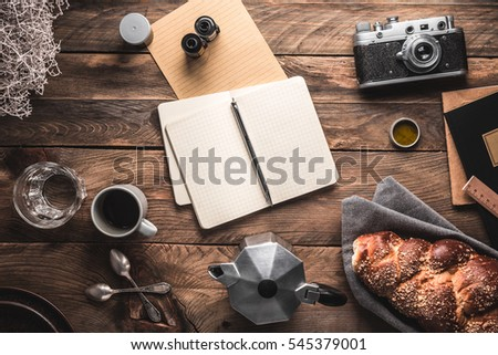 Notebook opened, cup of coffee, coffee maker, breakfast, camera on wooden boards. Flat lay with copy space.