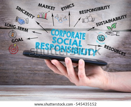 Corporate Social Responsibility Concept. Tablet computer in the hand. Old wooden background