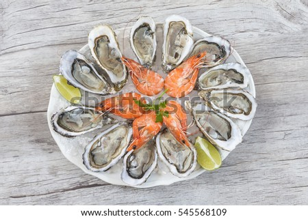 fresh oysters and shrimps on old wooden board  #545568109