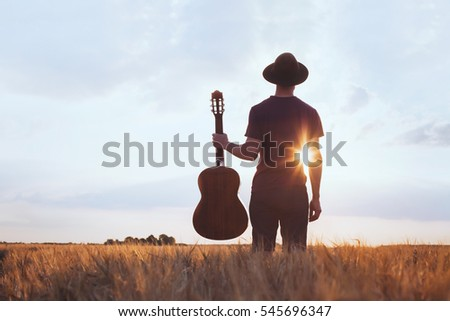 music festival background, silhouette of musician artist with acoustic guitar at sunset field  Royalty-Free Stock Photo #545696347