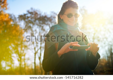 Gorgeous beautiful young caucasian woman messaging on the futuristic smart-phone device in the park outdoor background, chatting, using internet, soicial network, photo sharing services #545716282