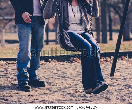 Couple on swing set in park.