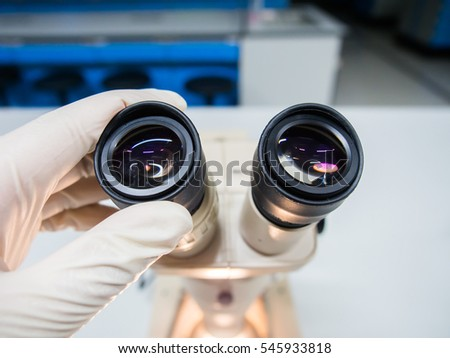 Scientist with stereoscopic microscope in microbiology laboratory #545933818