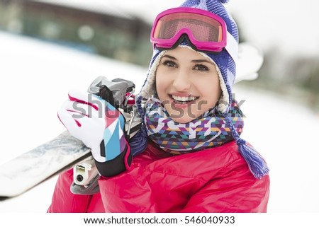 Beautiful young woman carrying skis in snow #546040933