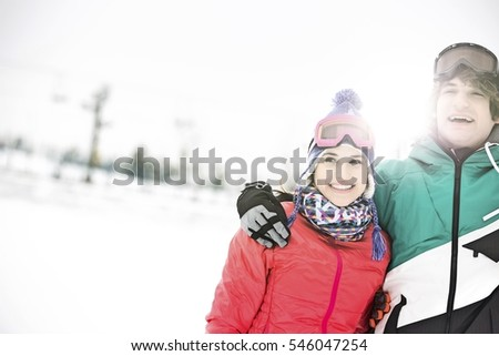Cheerful young couple standing arm around in snow #546047254