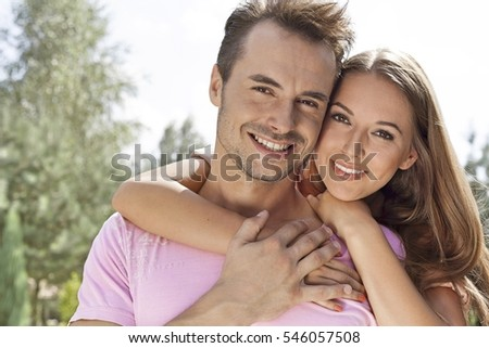 Portrait of beautiful young woman embracing man in park #546057508