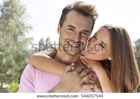 Beautiful young woman embracing man from behind in park #546057544