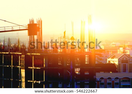 silhouette workers on background of construction in sunset. #546222667
