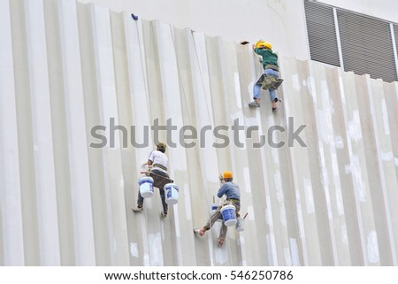 3 painters are hanging to paint with high building #546250786