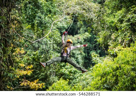 TOURIST adult wearing casual clothes Zip Line On Focus FOREST TRIP fun. #546288571
