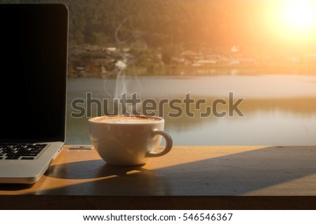 Coffee morning and laptop on wooden table with lake, mountain and village background.