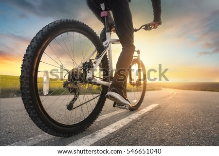Ride on bike on the road. Sport and active life concept in the summer time Royalty-Free Stock Photo #546651040