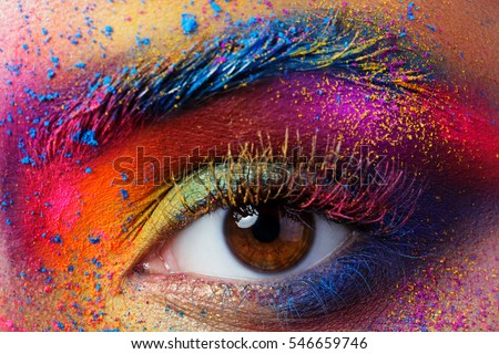 Close up view of female eye with bright multicolored fashion makeup. Holi indian color festival inspired. Studio macro shot Royalty-Free Stock Photo #546659746