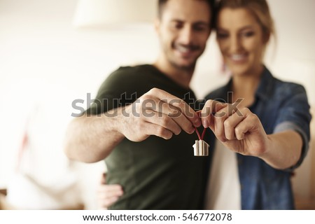 Couple holding key ring to their new house 